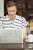 Smiling student with a hot drink using laptop — Stockfoto