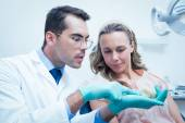 Male dentist showing woman prosthesis teeth — Stock Photo