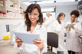 Science student holding tablet pc in lab — Foto de Stock