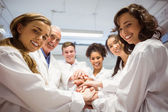 Science students and lecturer putting hands together — Stock Photo