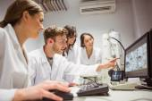 Science students looking at microscopic — Stock Photo