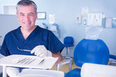 Dentist in blue scrubs holding tools — Stock Photo