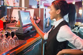 Pretty barmaid using touchscreen till  — Stock Photo