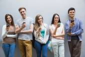 Students using their smartphones in a row — Stockfoto