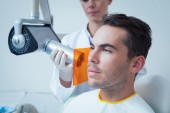 Serious young man undergoing dental checkup — Stock Photo