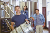 Young man holding keg with these colleagues behind him — Stock Photo