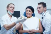 Dentists showing woman prosthesis teeth — Stock Photo
