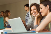 Smiling friends sitting using laptop — Stock Photo