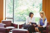 Businesswomen having a meeting and using tablet — Stock Photo