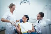 Male dentist with assistant shaking hands with woman — ストック写真