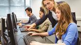 Atrakcyjny nauczyciel pomaga jej ucznia w klasie komputer — Zdjęcie stockowe