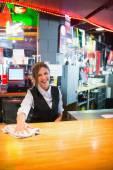 Pretty barmaid wiping down bar — Stock Photo