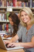Smiling mature female students using her laptop — Stock Photo