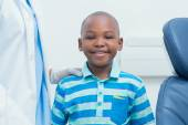 Smiling boy standing by cropped dentist — Stock Photo