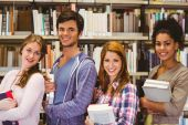 Students in a line smiling at camera holding books — Stock Photo