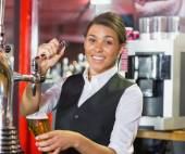 Pretty barmaid pulling pint of beer — Stock fotografie
