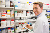 Handsome pharmacist writing on clipboard — Stock Photo