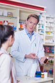 Pharmacist pointing a flask of pills — Stock Photo