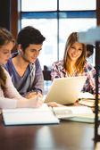 Student söker på kameran medan du studerar med klasskamrater — Stockfoto