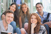 Happy students smiling at camera outside on campus — Stock Photo