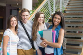Smiling students looking at camera outside — Stock Photo