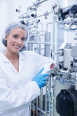 Smiling scientist leaning against gauge — Stock Photo