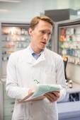 Focused pharmacist writing on clipboard — Φωτογραφία Αρχείου