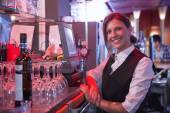 Happy barmaid using touchscreen till — Stock Photo