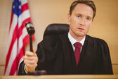 Serious judge about to bang gavel on sounding block — Stock Photo