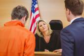 Lawyer speaking about the criminal in orange jumpsuit — Stock Photo