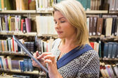 Mature student using tablet in library — Stock Photo