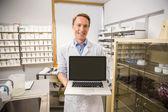 Happy pharmacist showing laptop screen — Stock Photo
