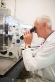 Biochemist using large microscope and computer — Stock Photo