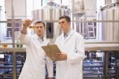 Focused scientist team looking at beaker — ストック写真