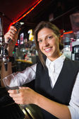 Happy barmaid pulling a pint of beer — Stok fotoğraf