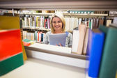 Mature student smiling in library — Stock Photo