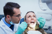 Dentist examining young womans teeth — Stock Photo