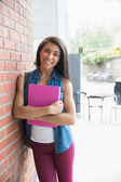 Pretty student smiling and holding notepads — Stock Photo