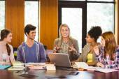 Smiling students and teacher in library — Stock Photo