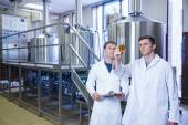Two men in lab coat looking at the beaker with beer — Stock Photo