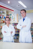 Pharmacist and his trainee standing — Stock Photo
