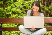 Smiling student sitting on bench listening music and using lapto — Stock Photo