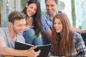 Happy students looking at smartphone — Stock Photo