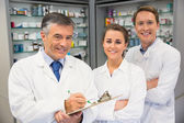 Team of pharmacists smiling at camera — Stock Photo