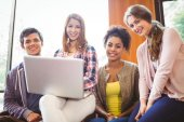 Smiling students sitting on couch using laptop — Stock Photo
