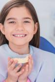 Smiling young patient holding teeth — Stock Photo