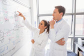 Science student and lecturer looking at whiteboard — Stock Photo