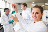 Young scientist holding up beaker — Stock Photo
