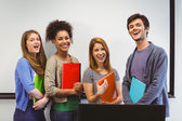 Students standing and smiling at camera holding notepads — Stock Photo