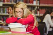Thoughtful mature student leaning on a stack of books — Stock Photo